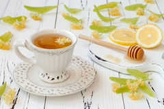 Cup of herbal tea with linden flowers, lemon and honey on a old wooden background. Royalty Free Stock Photography
