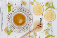 Cup of herbal tea with linden flowers, lemon and honey on a old wooden background. Top view Stock Photography
