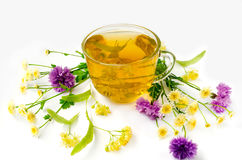 A cup of herbal tea with linden and wildflowers. On a white background Stock Photos