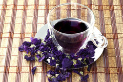 Cup of herbal tea of mauve flowers dry. Bamboo table cloth Stock Photography