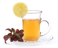 Cup of herbal tea with red tulsi leaves and lemon royalty free stock photos