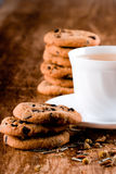Cup of herbal tea and some fresh cookies. Closeup on wooden table Royalty Free Stock Photo