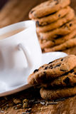 Cup of herbal tea and some fresh cookies. Closeup on wooden table Royalty Free Stock Photos