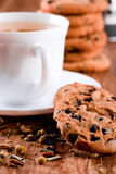 Cup of herbal tea and some fresh cookies. Closeup on wooden table Royalty Free Stock Images