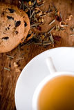 Cup of herbal tea and some fresh cookies. Closeup on wooden table Royalty Free Stock Image