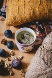 Cup with herbal tea and sweaters, figs and nuts Royalty Free Stock Photos