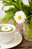 Cup of herbal tea with wild camomiles, mint and flowers Royalty Free Stock Photos