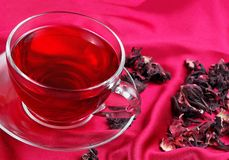 Cup of hibiscus tea on a red silk background. top view. cold and flu remedy stock images