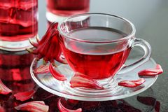 Cup of hibiscus tea rosella, karkade, red sorrel on table. Cup of hibiscus tea rosella, karkade, red sorrel, Agua de flor de Jamaica on table. Drink made from stock images