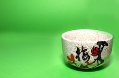 Cup with a hieroglyph on a green background. On a cup painted Chinese plum Royalty Free Stock Images