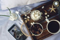 Cup of homemade cocoa with marshmallow, chocolate, flowers and smartphone on rustic wooden tray in the cozy bed Royalty Free Stock Photos