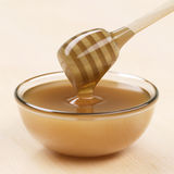 Cup of honey with dipper Royalty Free Stock Image