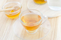 A cup of honey tea with honey on wooden table Royalty Free Stock Photo