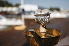 Cup of hookah with burning coals on the background of white yachts royalty free stock photo