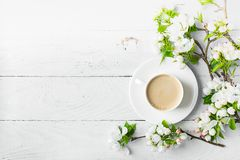 A cup of hot aromatic coffee and blossoming branches of an apple tree on a wooden white background. Flat lay royalty free stock photography