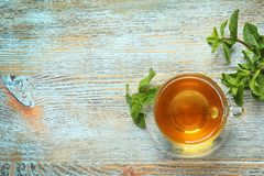 Cup with hot aromatic mint tea and fresh leaves. On wooden table, top view royalty free stock image