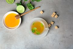 Cup of hot aromatic tea with mint and honey on table stock photo