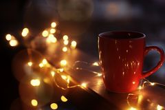 Cup of hot beverage on balcony railing decorated with Christmas lights, space for text. Winter evening royalty free stock image
