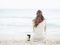 Cup of hot beverage near woman in sweater sitting on lonely beach Royalty Free Stock Photo