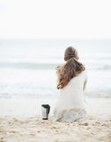 Cup of hot beverage near young woman in sweater sitting on beach Royalty Free Stock Photography