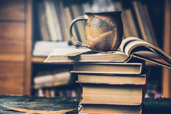 Cup with hot beverage and steam on a stack of books in the library Royalty Free Stock Images