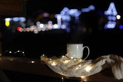 Cup of hot beverage, sweater and Christmas lights on wooden railing outdoors against blurred background, space for text. royalty free stock image