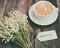 Cup of hot black coffee and a bouquet of fresh lilies of the val Stock Photo