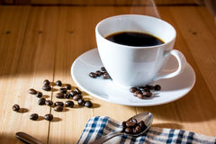 Cup of hot black coffee with the roasted coffee beans. White cup of hot black coffee with the roasted coffee beans on wooden table. Spoon and coffee bean on Royalty Free Stock Photos