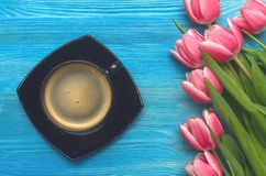 Cup of hot black coffee and tulip flowers on wooden background. Romantic breakfast concept background. Cup of hot black coffee and tulip flowers on blue wooden Stock Image