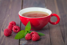 Cup of hot black  tea with mint and raspberry Royalty Free Stock Photography
