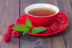 Cup of hot black  tea with mint and raspberry Royalty Free Stock Image