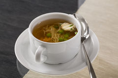 A cup of hot broth, with noodles, and vegetables decorated for g Royalty Free Stock Photo