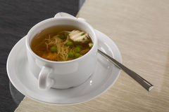 A cup of hot broth, with noodles, and vegetables decorated for g Royalty Free Stock Photos