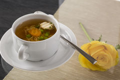 A cup of hot broth, with noodles, and vegetables decorated for g Stock Photo