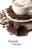 Cup of hot cappuccino and coffee beans Royalty Free Stock Photography