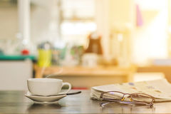 Cup of hot cappuccino coffee. Closeup cup of hot cappuccino coffee with newspaper and spectacles on the wood table with blur kitchen room background-warm tone Stock Images