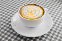 Cup of hot Cappuccino Coffee with Latte Art on plaid table. Stock Image