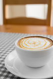 Cup of hot Cappuccino Coffee with Latte Art on plaid table. Royalty Free Stock Photos