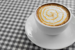 Cup of hot Cappuccino Coffee with Latte Art on plaid table. Stock Photos