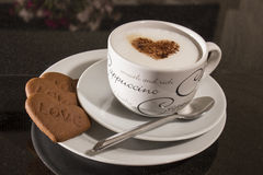 Love Cappuccino. Cup of hot Cappuccino coffee with love biscuits stock photo