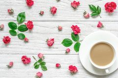 Cup of hot cappuccino or coffee with milk on white saucer with flowers composition made of pink rose flowers. With green leaves. Valentine`s day background Royalty Free Stock Photo