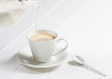 Cup of hot cappuccino coffee on a white wood table. Royalty Free Stock Photos