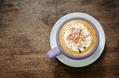 Cup of Hot Cappuccino Coffee On Wood Table. A violet cup of hot cappuccino coffee on old wood table Royalty Free Stock Photography