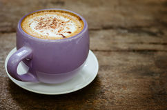 Cup of Hot Cappuccino Coffee On Wood Table. A violet cup of hot cappuccino coffee on old wood table Royalty Free Stock Images