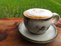 Cup of hot cappuccino on the wooden table with paddy field Stock Photography