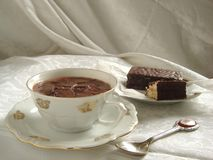 Cup of hot chocolate. Porcelain cup of hot chocolate served with chocolate cake stock photo