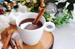 A Cup of Hot Chocolate with Cinnamon Stick. Close up a cup of hot chocolate with cinnamon stick on wooden board stock image
