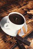 Cup of hot chocolate, cinnamon sticks, nuts and chocolate on woo. Den table on brown background Stock Photos
