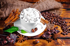 Cup of hot chocolate, cinnamon sticks, nuts and chocolate on woo. Den table on brown background stock photo