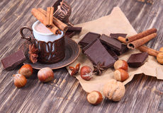 Cup of hot chocolate, cinnamon sticks, nuts and chocolate on wooden table on brown background Royalty Free Stock Photography